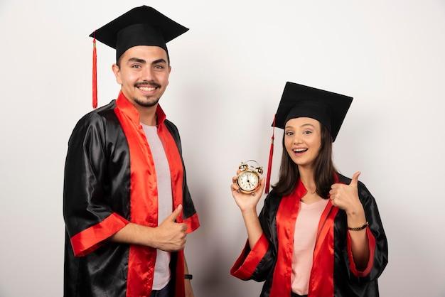 Gelukkige studenten in toga met klok die zich op wit bevindt.
