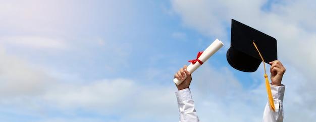 Gelukkige studenten in toga vieren afstuderen en gooien hun handen omhoog en een pet in de lucht