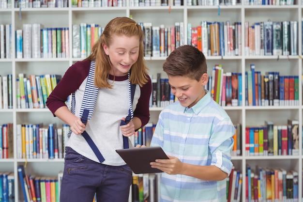 Gelukkige studenten met behulp van digitale tablet in bibliotheek