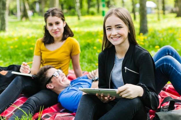 Gelukkige studenten rusten in het park