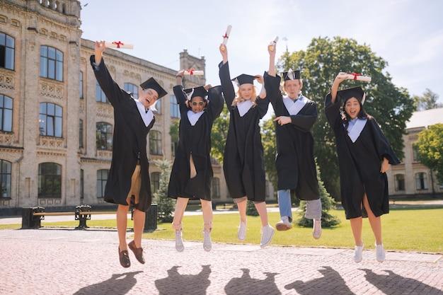 Gelukkige studenten springen in de lucht in de tuin, enthousiast over hun afstuderen