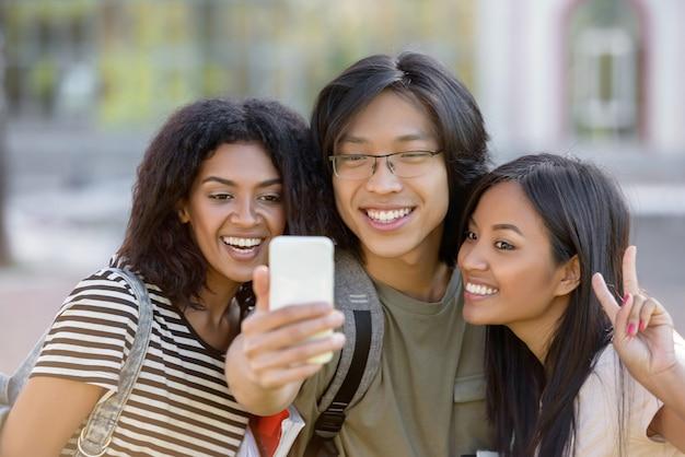 Gelukkige studenten staan en maken selfie buitenshuis