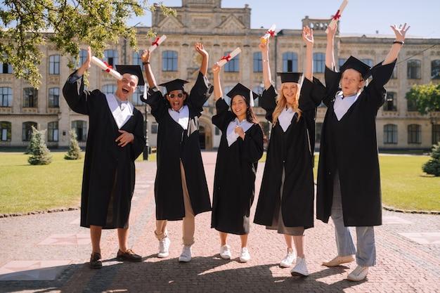 Gelukkige studenten staan samen met hun handen in de lucht voor de universiteit
