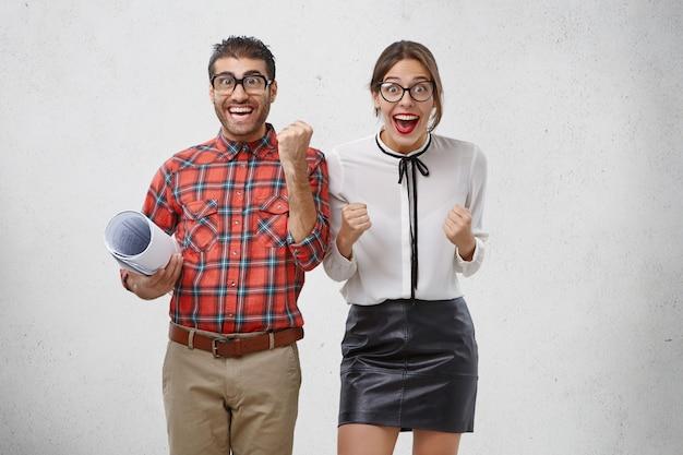 Gelukkige studenten verheugen zich met succes geslaagd voor examens en toekomstige vakanties, balken vreugdevol vuisten