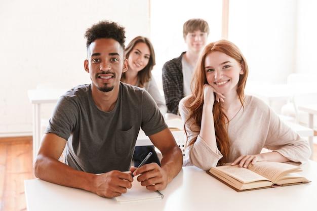 Gelukkige studenten zitten in de klas binnenshuis op zoek naar camera.