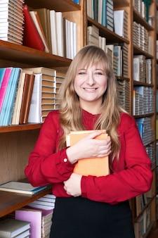 Gelukkige studentenvrouw die een boek houdt