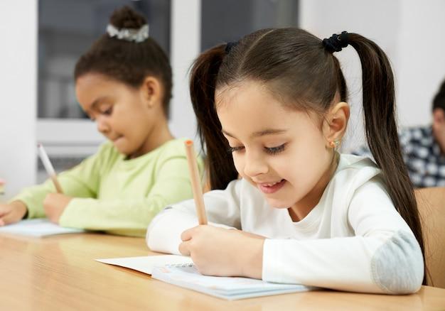 Gelukkige studentenzitting bij lijst en het schrijven in voorbeeldenboek