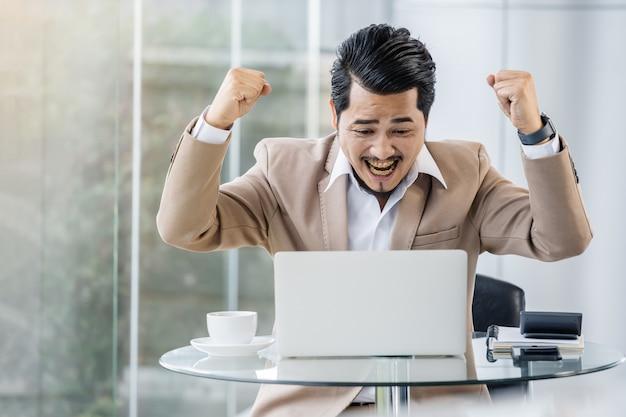 Gelukkige succesvolle bedrijfsmens die laptop computer met behulp van