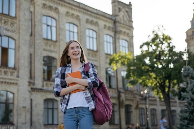 Gelukkige succesvolle student met rugzak en boeken die aan universiteit, onderwijsconcept lopen