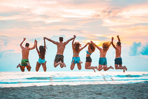 Gelukkige succesvolle vrienden die op het strand springen