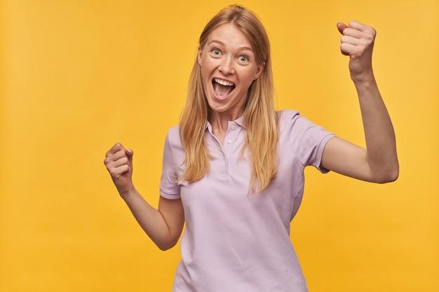 Gelukkige succesvolle vrouw met sproeten in lavendelt-shirt die handen opheft die en overwinning op geel schreeuwen vieren