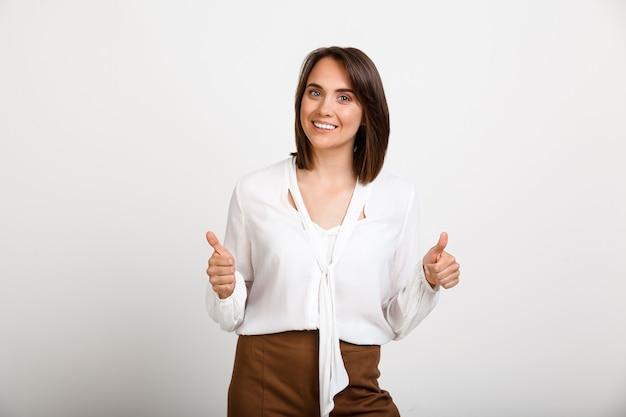 Gelukkige succesvolle vrouw thumbs-up, geef goedkeuring