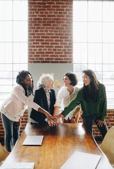 Gelukkige succesvolle vrouwen die handen stapelen