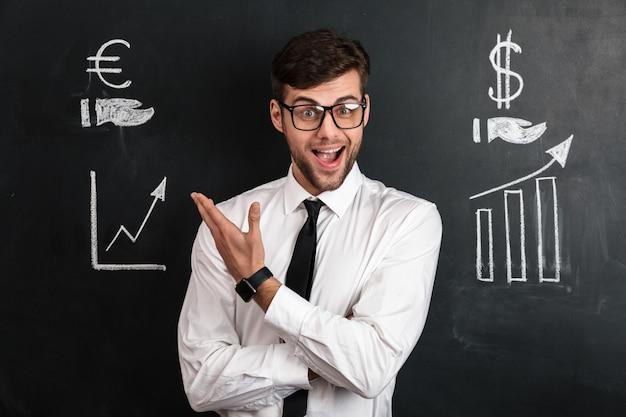 Gelukkige succesvolle zakenman die in wit overhemd financiële regeling voorstelt