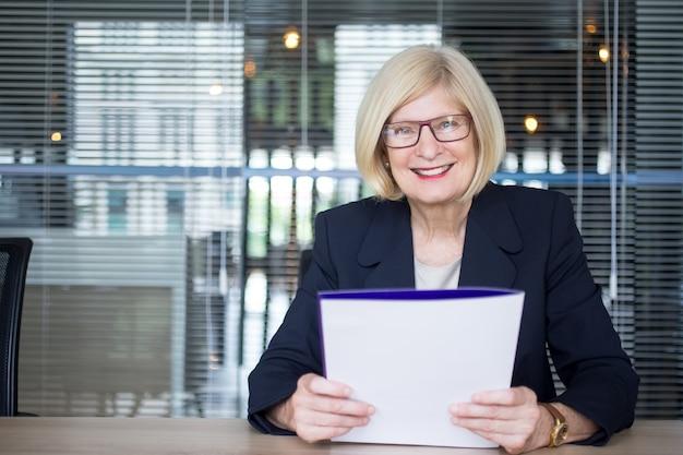 Gelukkige succesvolle zakenvrouw doet papierwerk