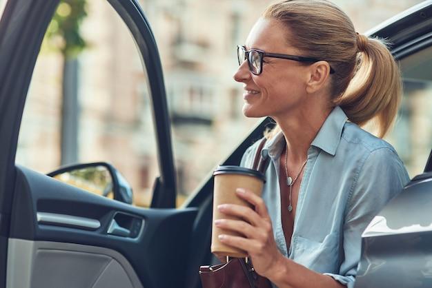 Gelukkige succesvolle zakenvrouw van middelbare leeftijd die een papieren kopje koffie vasthoudt terwijl ze uit haar stapt