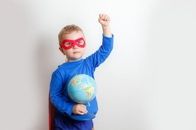 Gelukkige super heldenjongen die een bol in zijn hand houdt, het concept de wereld te redden