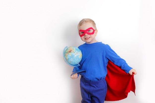 Gelukkige super heldenjongen die een bol in zijn hand houdt, het concept om de wereld op een witte achtergrond te redden