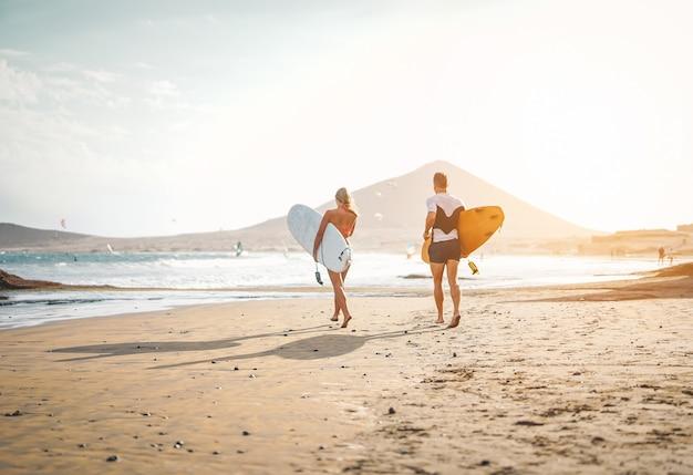 Gelukkige surfers die met surfplanken op het strand lopen