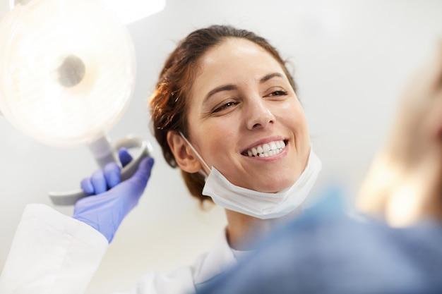 Gelukkige tandarts die patiënt bekijkt