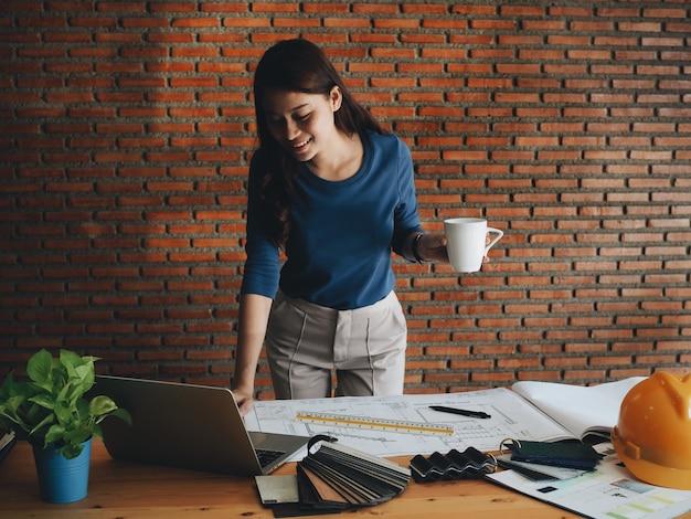 Gelukkige techniekvrouw het drinken koffie op kantoor.