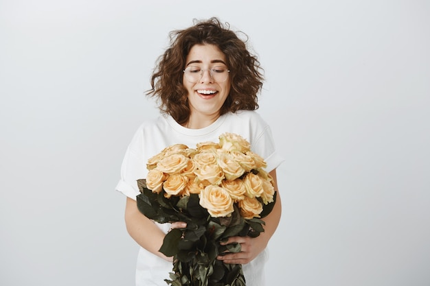 Gelukkige tedere vriendin ontvangt een boeket prachtige bloemen, houdt rozen vast en zuchtend verbaasd