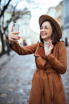 Gelukkige tedere vrouw die foto op haar telefoon in de herfstdag buiten nemen