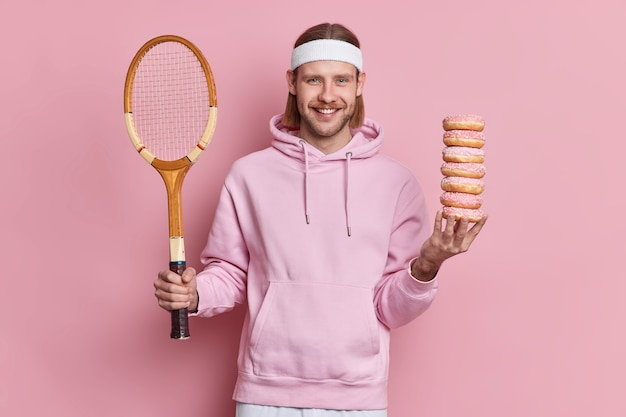 Gelukkige tennisser kiest tussen gezonde levensstijl en schadelijk voedsel houdt racket vast en stapel zoete donuts draagt sweatshirt en hoofdband. europese bebaarde man gaat badmintonspel spelen