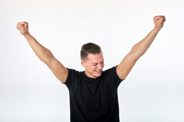 Gelukkige tevreden jonge mens die en een succes uitspreidende handen met vreugde vieren toejuichen