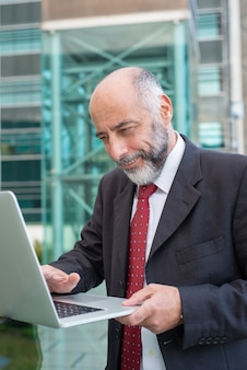 Gelukkige tevreden rijpe zakenman met laptop het letten op inhoud