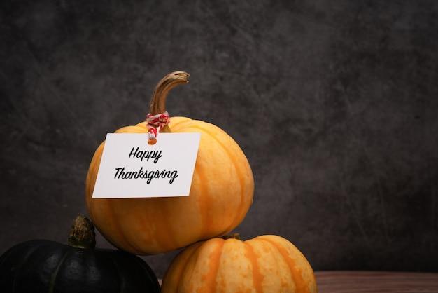 Gelukkige thanksgiving met pompoenen op donkere achtergrond