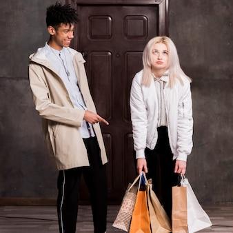 Gelukkige tiener die bij zijn vermoeid meisje lachen die vele het winkelen zakken in hand houden