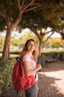 Gelukkige tiener die met rugzak in park glimlacht