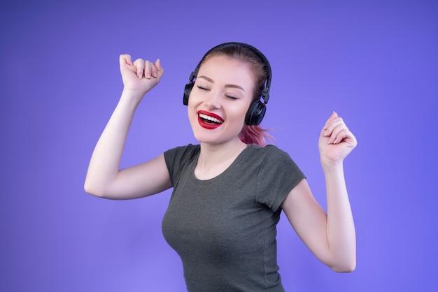 Gelukkige tiener die van muziek met gesloten ogen en geopende mond geniet