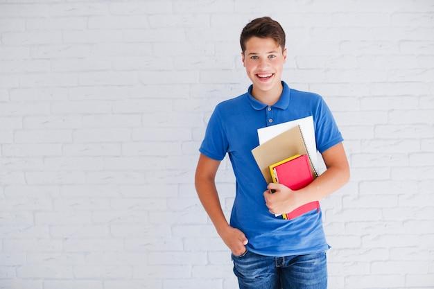 Gelukkige tiener met boeken kijken naar camera
