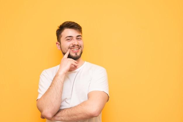 Gelukkige tiener met een baard draagt een wit t-shirt, staat op geel