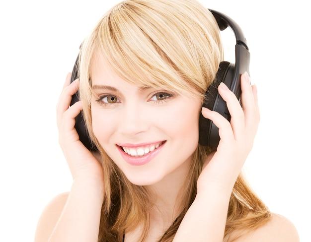 Gelukkige tiener vrouw in koptelefoon over wit