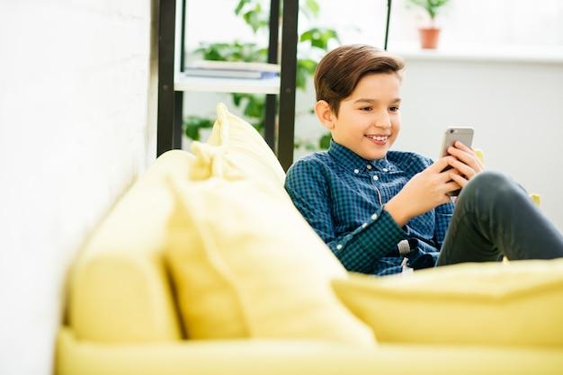 Gelukkige tiener zittend op de bank met een smartphone in zijn handen en glimlachen terwijl hij naar het scherm ervan kijkt