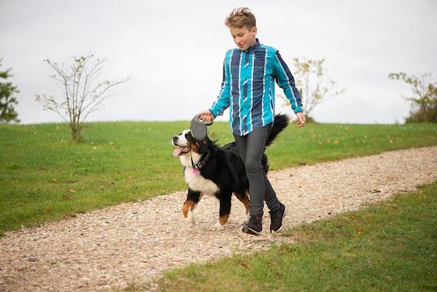 Gelukkige tienerjongen die met berner sennenhond loopt. vriendschap van mensen met een huisdier.