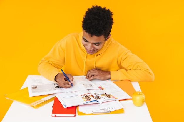 Gelukkige tienerjongen die studeert terwijl hij aan het bureau zit en in een leerboek schrijft dat over een gele muur is geïsoleerd