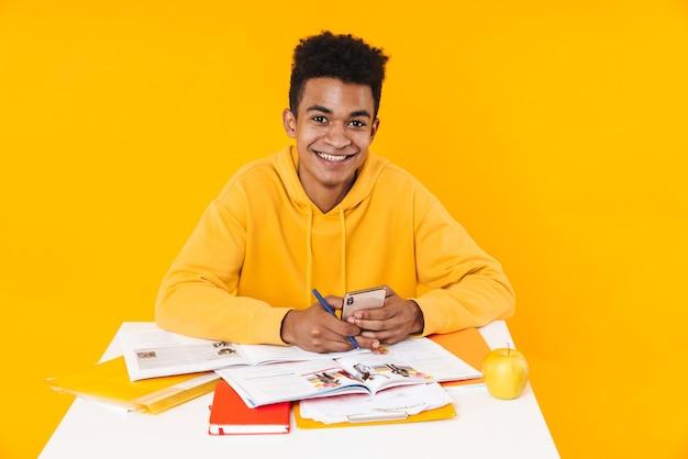 Gelukkige tienerjongen die studeert terwijl hij aan het bureau zit met schoolboeken geïsoleerd over gele muur, met behulp van mobiele telefoon