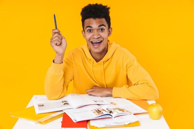 Gelukkige tienerjongen die studeert terwijl hij aan het bureau zit met schoolboeken geïsoleerd over gele muur, met een pen