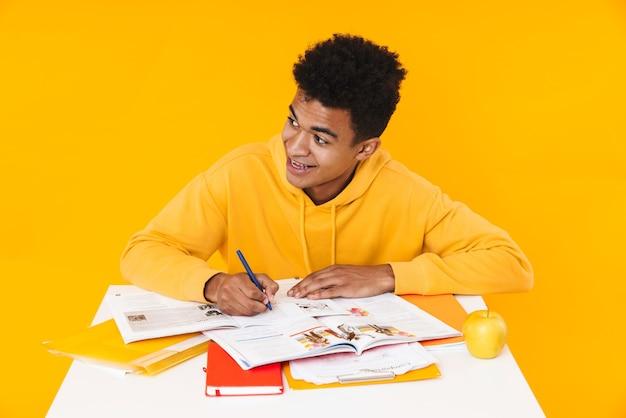 Gelukkige tienerjongen die studeert terwijl hij aan het bureau zit met schoolboeken geïsoleerd over gele muur, schrijven