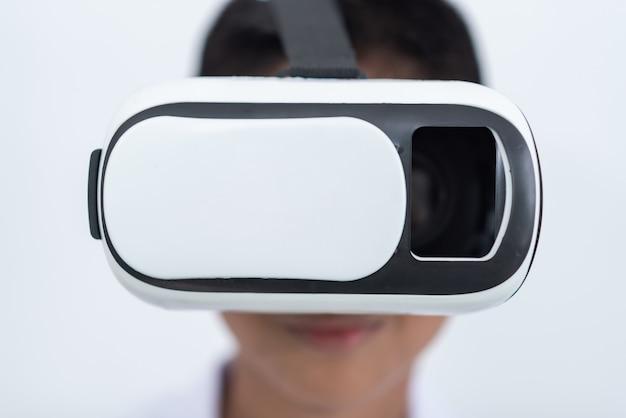 Gelukkige tienerjongen die virtuele werkelijkheid het letten op films draagt of videospelletjes speelt