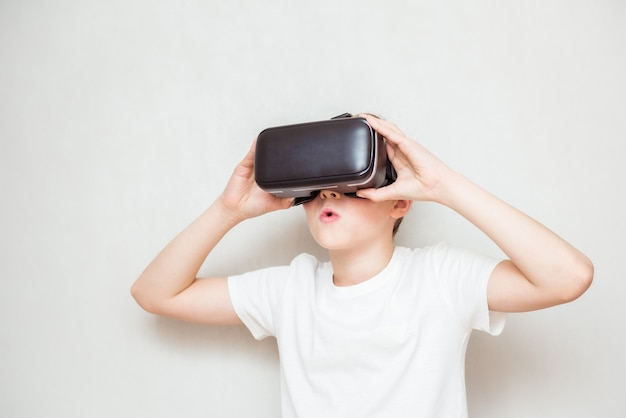 Gelukkige tienerjongen die vr-bril draagt, films kijkt of videospelletjes speelt, geïsoleerd op wit. vrolijke tiener die in vr-bril kijkt. grappig kind dat 3d-gadgettechnologie ervaart