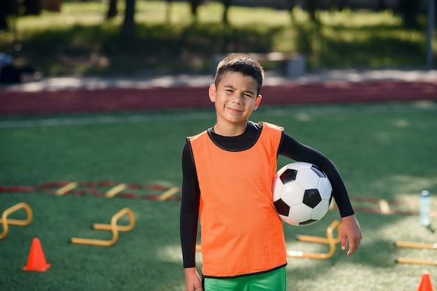 Gelukkige tienerjongen in voetbaluniform houdt een bal na de ochtendtraining in het stadion