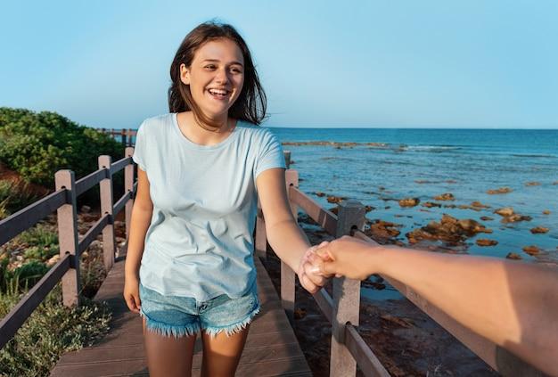 Gelukkige tienermeisjes lopen op de stoep aan zee. glimlachende jonge vrouwen hand in hand en wandelen bij zonsondergang, driekwart lengte schot. t-shirtmodel