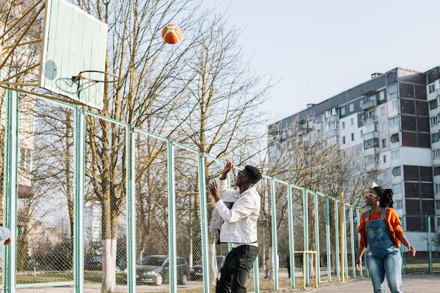 Gelukkige tieners die basketbal in openlucht spelen