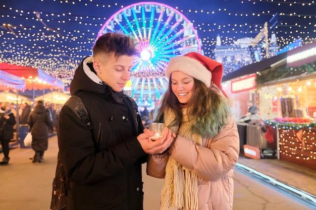 Gelukkige tieners koppelen jongen en meisje in kerstmanhoed bij de verwarmende handen van de kerstmismarkt met kaars