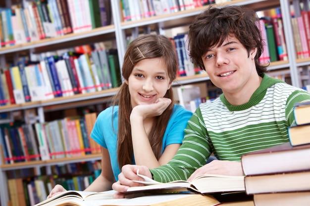 Gelukkige tieners met boekenplanken achtergrond